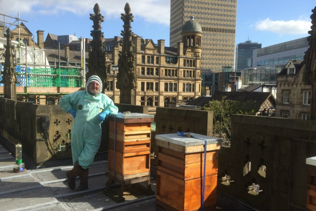 Honorary Canon Adrian Rhodes with his beehives on the roof of Manchester Cathedral. Credit: Copyright 2015 Clarissa Hyman