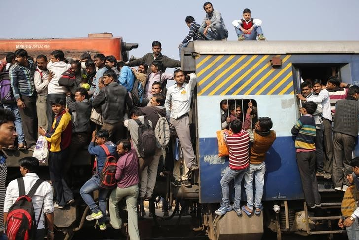 Passengers board an overcrowded train near a railway station at Loni town in Uttar Pradesh, February 24, 2016. REUTERS/Anindito Mukherjee