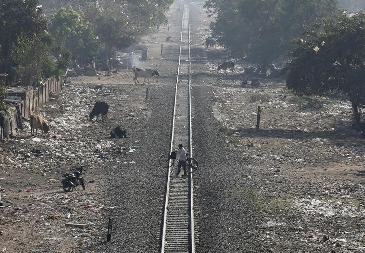 A man carries his bicycle as he crosses a railway track in Ahmedabad, February 24, 2016. REUTERS/Amit Dave