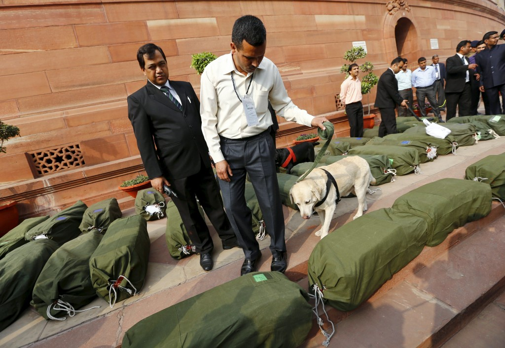 Security force personnel use as a sniffer dog to check bags containing budget papers inside the parliament premises in New Delhi, India, February 29, 2016. REUTERS/Adnan Abidi