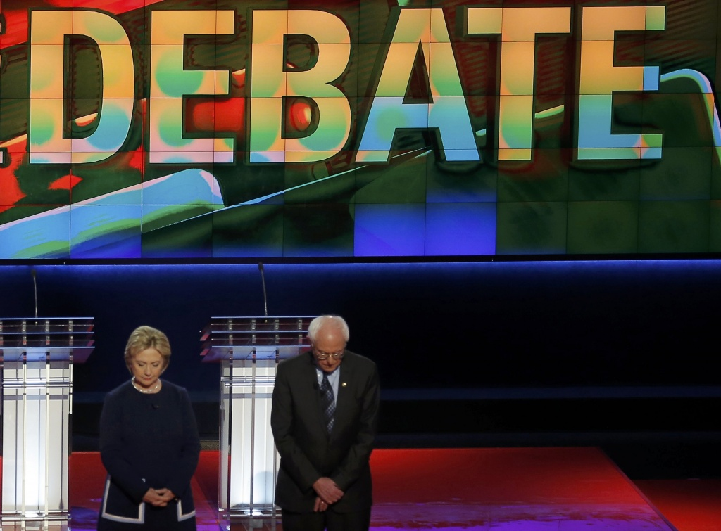 Democratic U.S. presidential candidates Hillary Clinton and U.S. Senator Bernie Sanders observe a moment of silence for the late U.S. first lady Nancy Reagan before the start of the Democratic U.S. presidential candidates' debate in Flint, Michigan, March 6, 2016. REUTERS/Jim Young