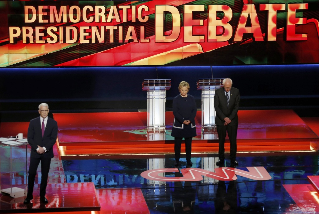 Democratic U.S. presidential candidates Hillary Clinton and U.S. Senator Bernie Sanders observe a moment of silence for the late U.S. first lady Nancy Reagan as moderator Anderson Cooper looks on before the start of the Democratic U.S. presidential candidates' debate in Flint, Michigan, March 6, 2016. REUTERS/Jim Young