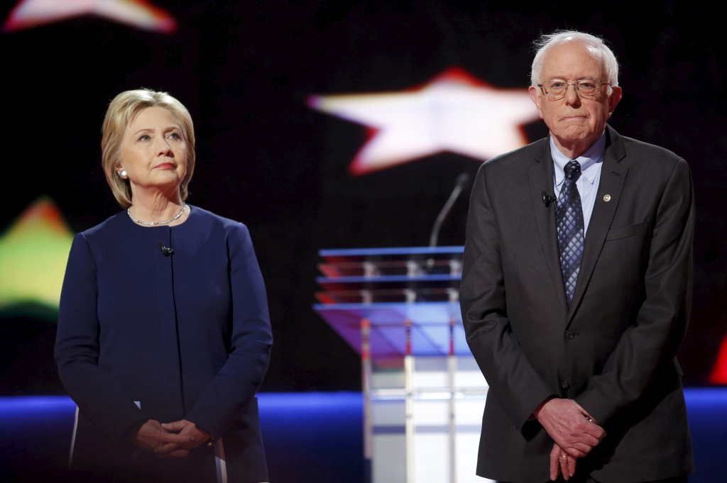 Democratic U.S. presidential candidates Hillary Clinton and Bernie Sanders pose together onstage at the start of the U.S. Democratic presidential candidates' debate in Flint, Michigan, March 6, 2016. REUTERS/Carlos Barria