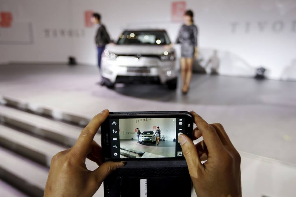 A man takes a photograph of Ssangyong Motor Co's Tivoli during its launch ceremony in Seoul in this January 13, 2015 file photo. REUTERS/Kim Hong-Ji/Files