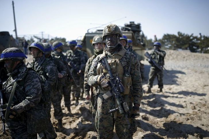 South Korean (blue headbands) and U.S. Marines take part in a U.S.-South Korea joint landing operation drill in Pohang, South Korea, March 12, 2016. REUTERS/Kim Hong-Ji