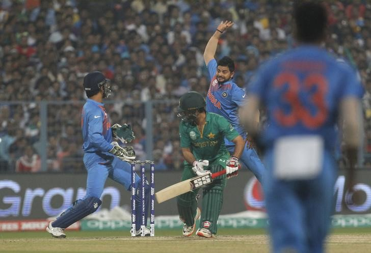 Cricket - India v Pakistan- World Twenty20 cricket tournament - Kolkata, 19/03/2016. Suresh Raina (2nd R) jumps to field the ball off the bat of Pakistan's Ahmed Shehzad as India's captain and wicketkeeper Mahendra Singh Dhoni (L) looks on. REUTERS/Rupak De Chowdhuri