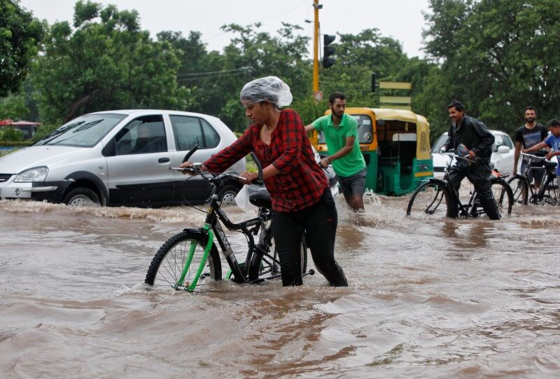 People commute through a flooded road after heavy rains in Chandigarh, India, June 28, 2016. REUTERS/Ajay Verma